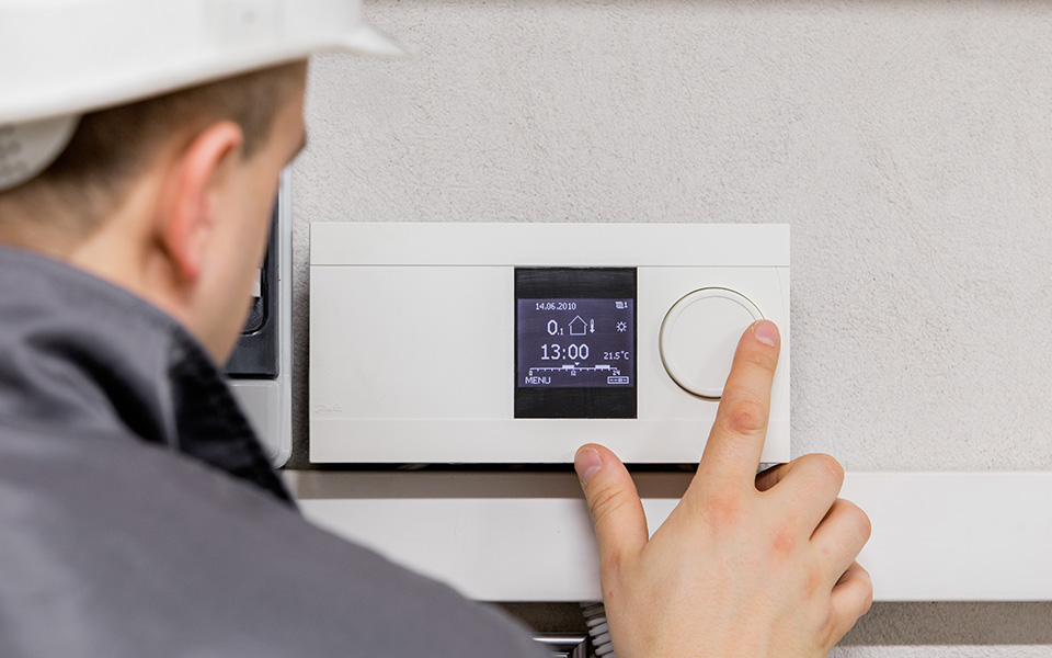 man operating a thermostat on the wall